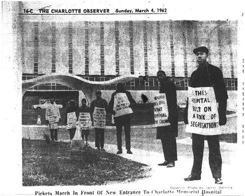 Photo from The Charlotte Observer story - Unidentified Man Tears Signs of Negro Pickets at Hospital